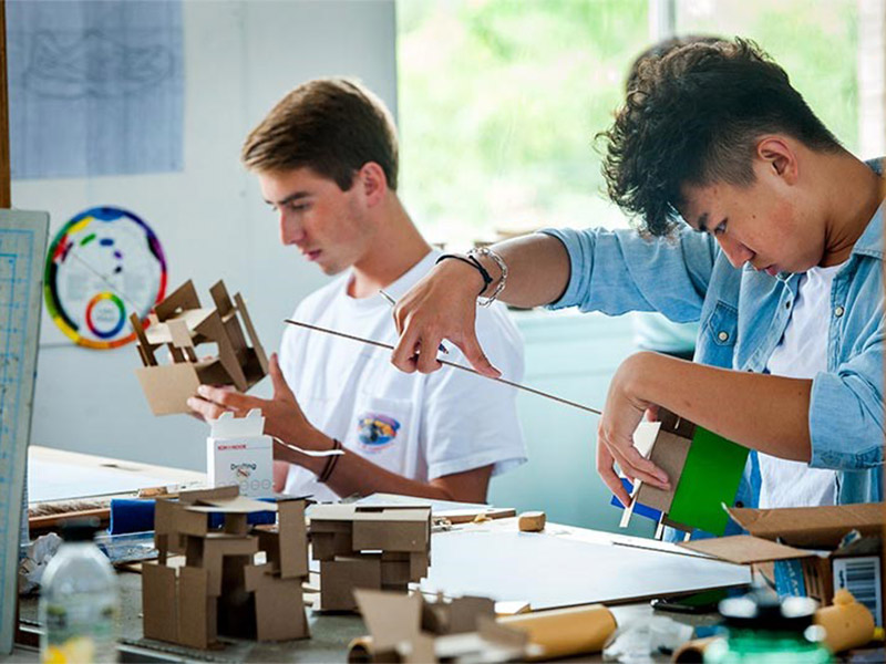 Two male architecture students assemble cardboard models of cube designs sitting at a studio desk with a window in the background