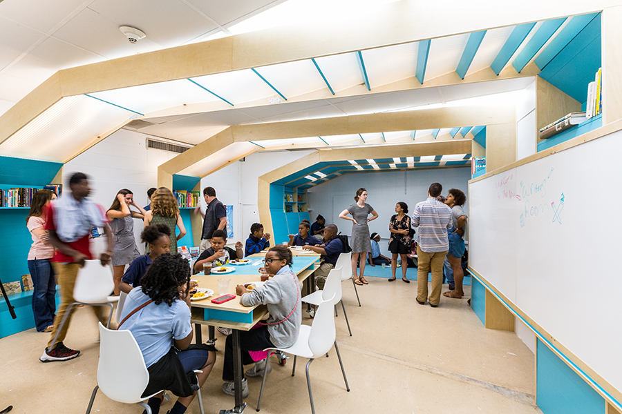 Adults and children sitting and standing inside a modern, brightly lit classroom with child size tables and chairs and a large white board on the right-hand wall that stretches the length of the room
