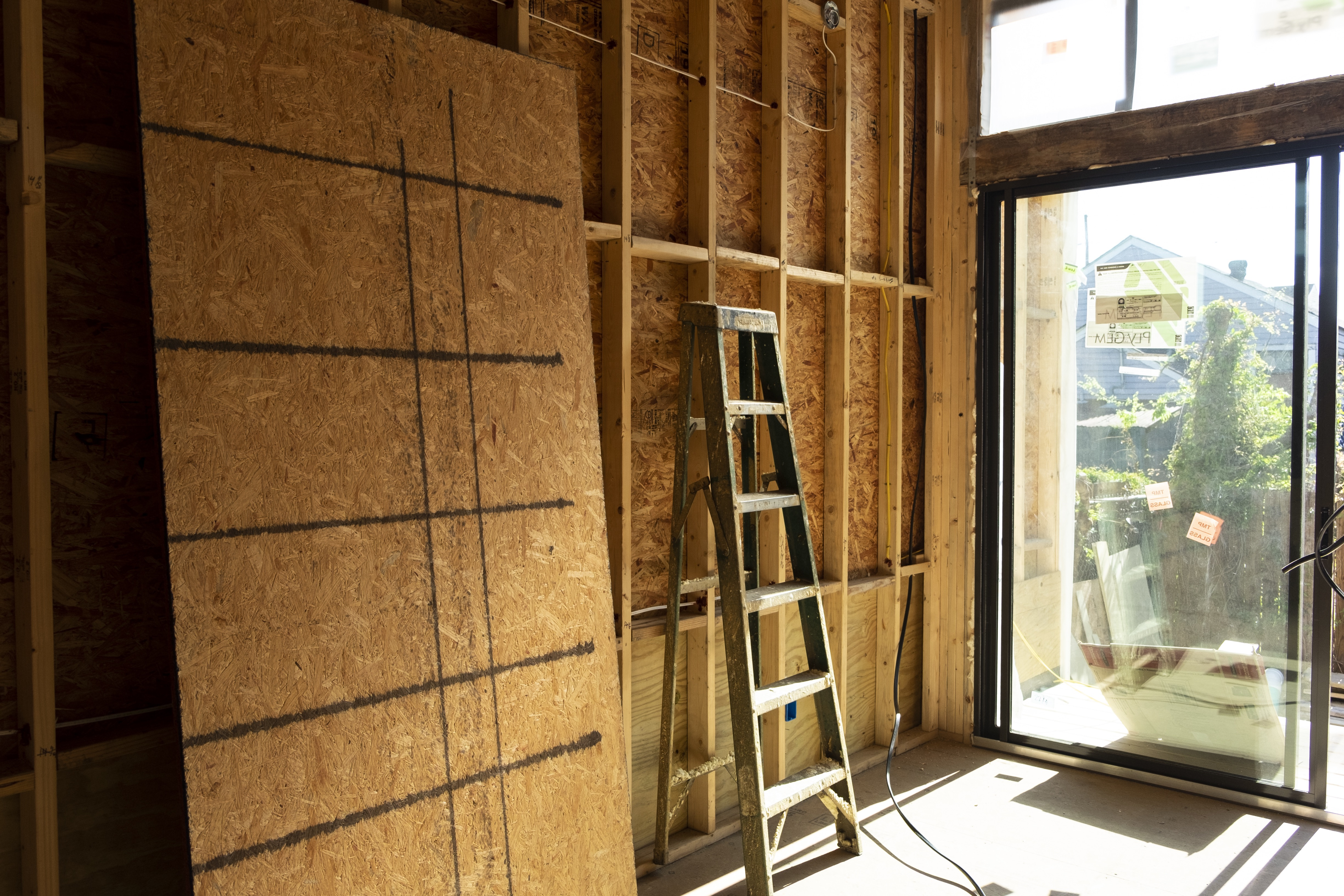 Interior view of home under construction with light coming in through a large window