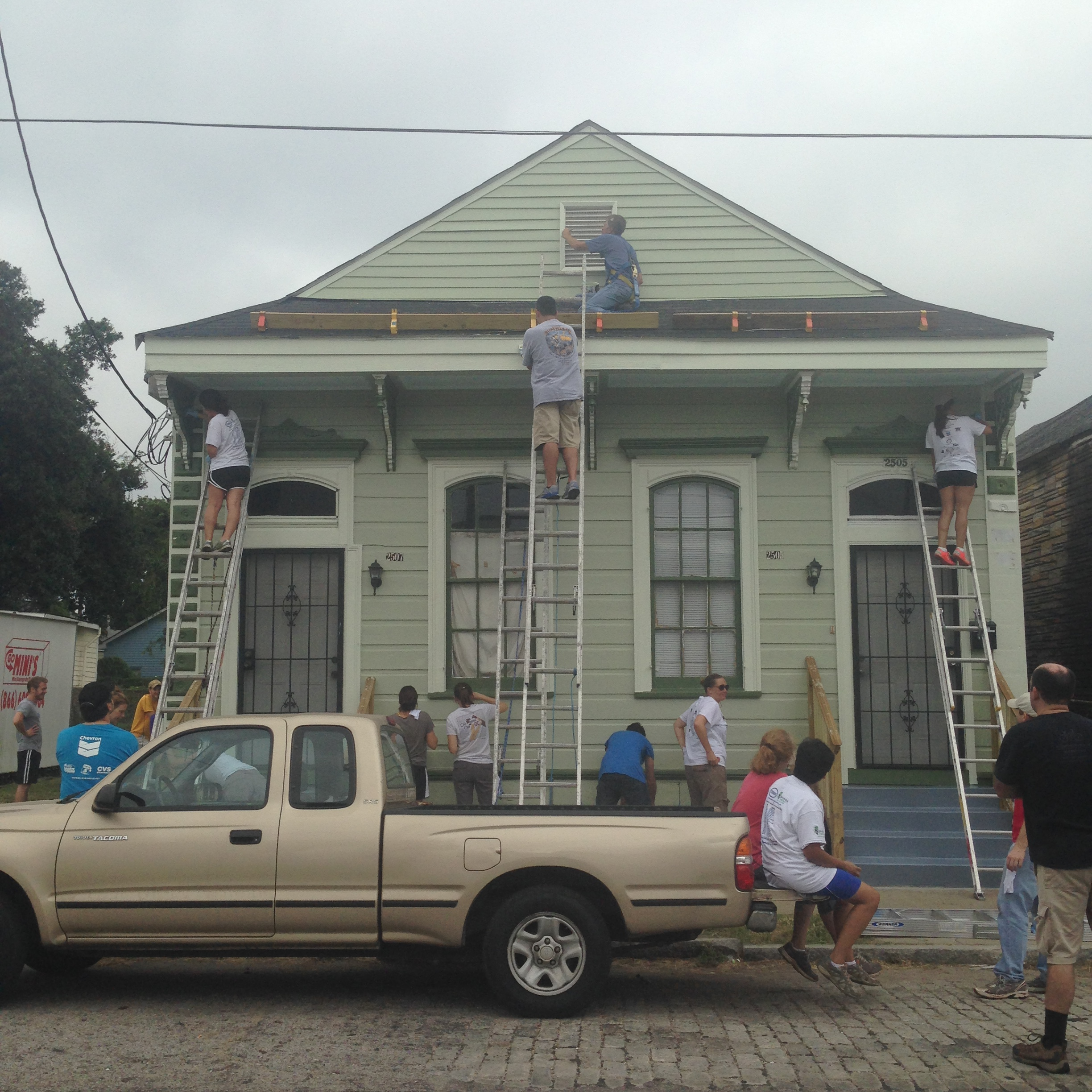students on ladders and sidewalk painting exterior of double shotgun house