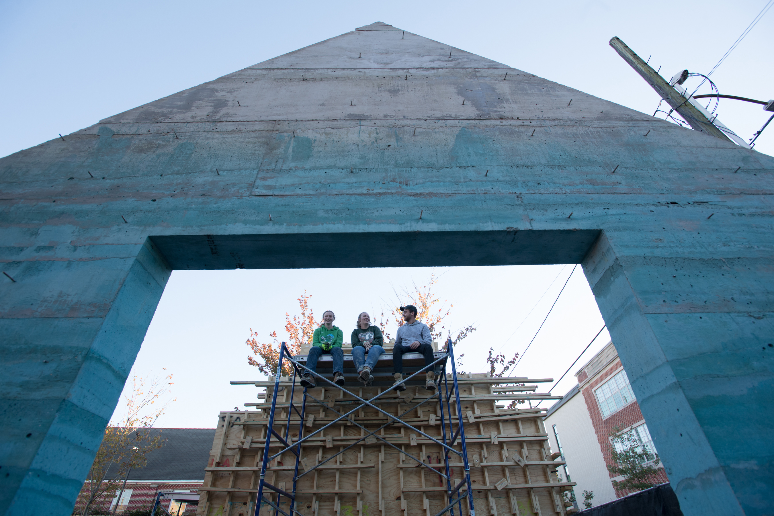 three students sitting on scaffold behind concrete facade