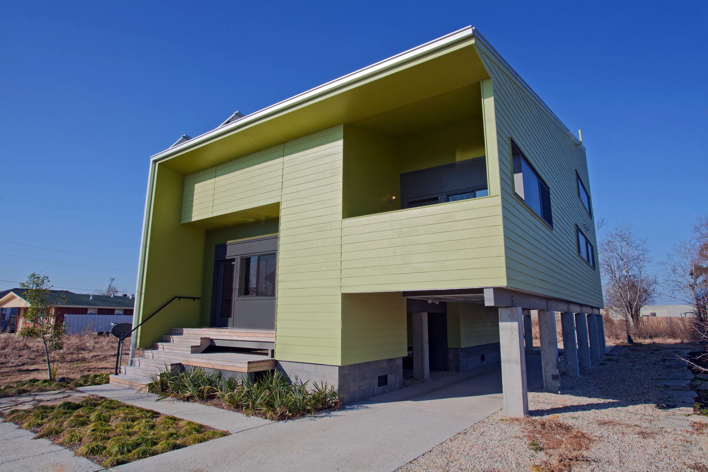 Front view of a modern two-story home with carport on onesie and steps up the front door on the other side