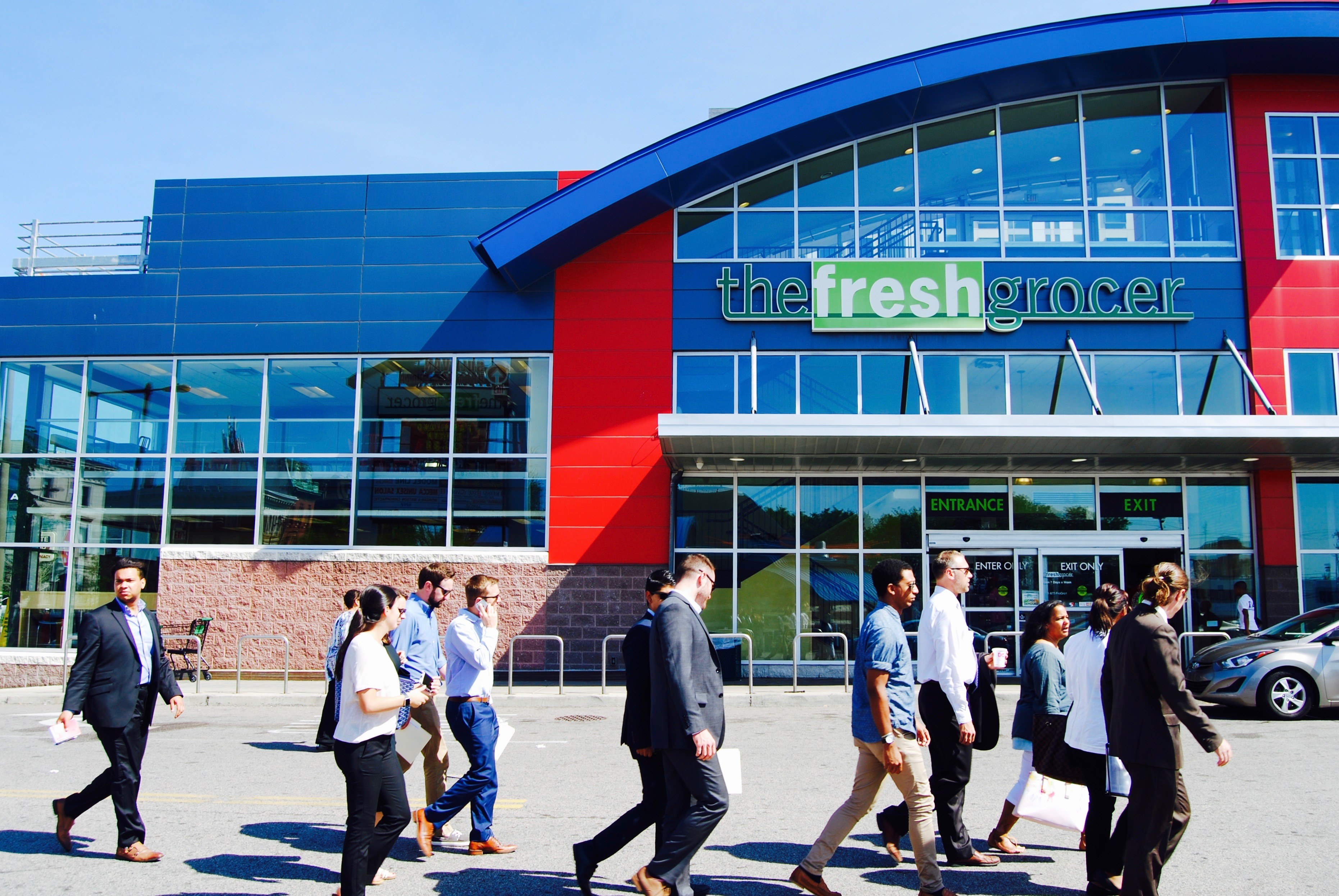 Students and faculty walking through parking lot in front of Fresh Grocer building