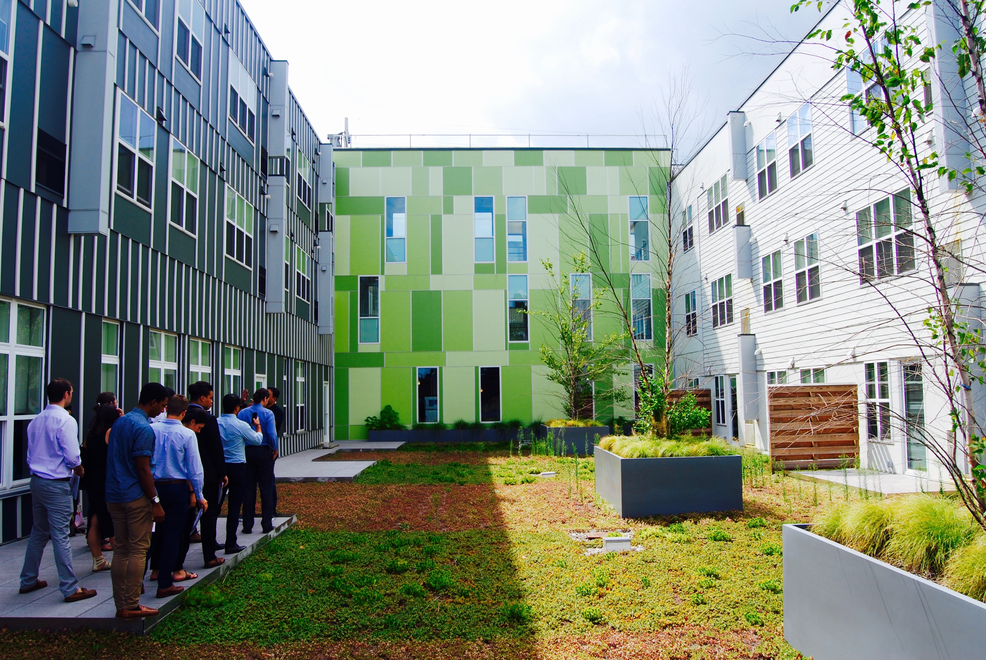 tour group in shady courtyard surrounded by three story buildings