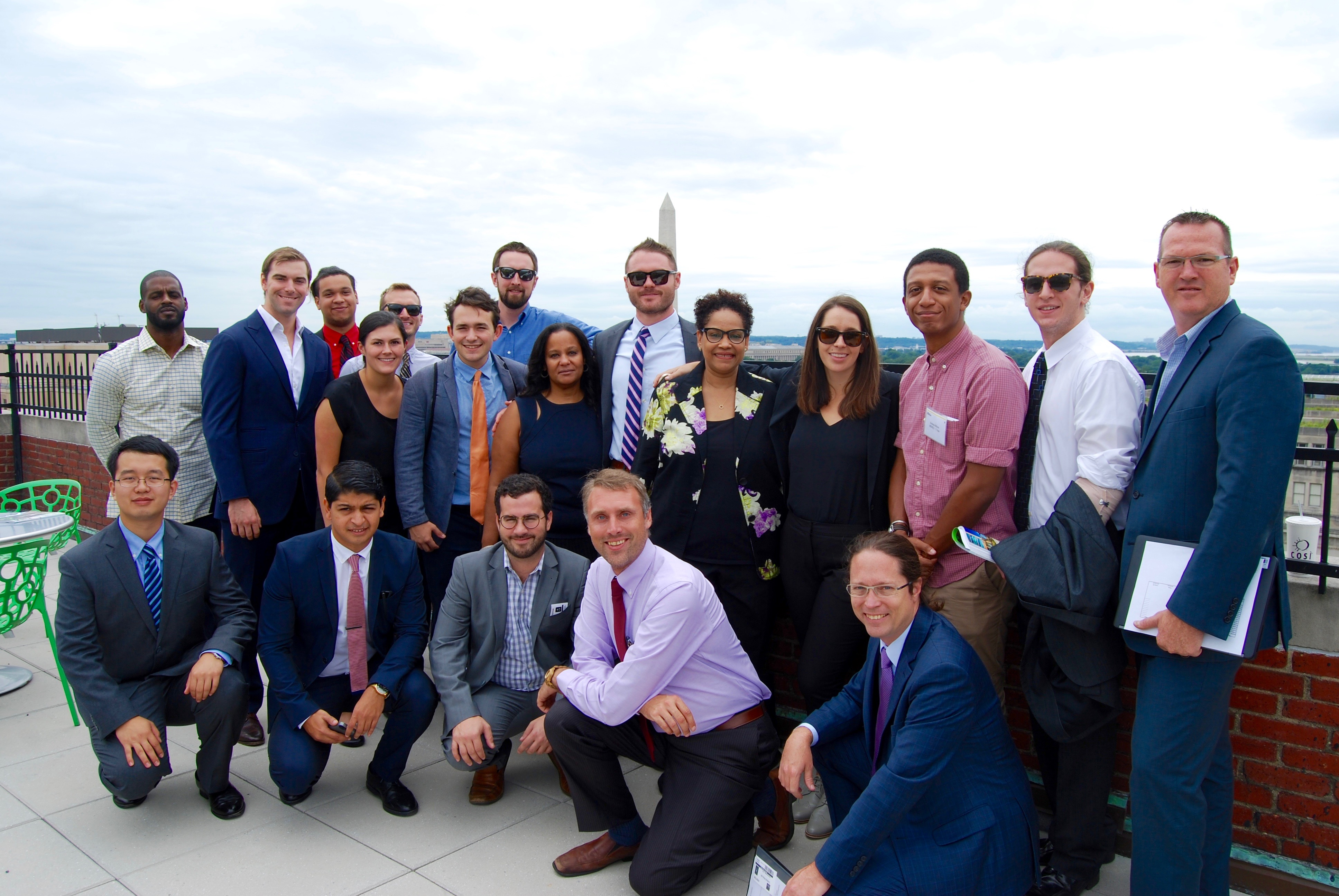 students and faculty on rooftop patio near Washington Monument
