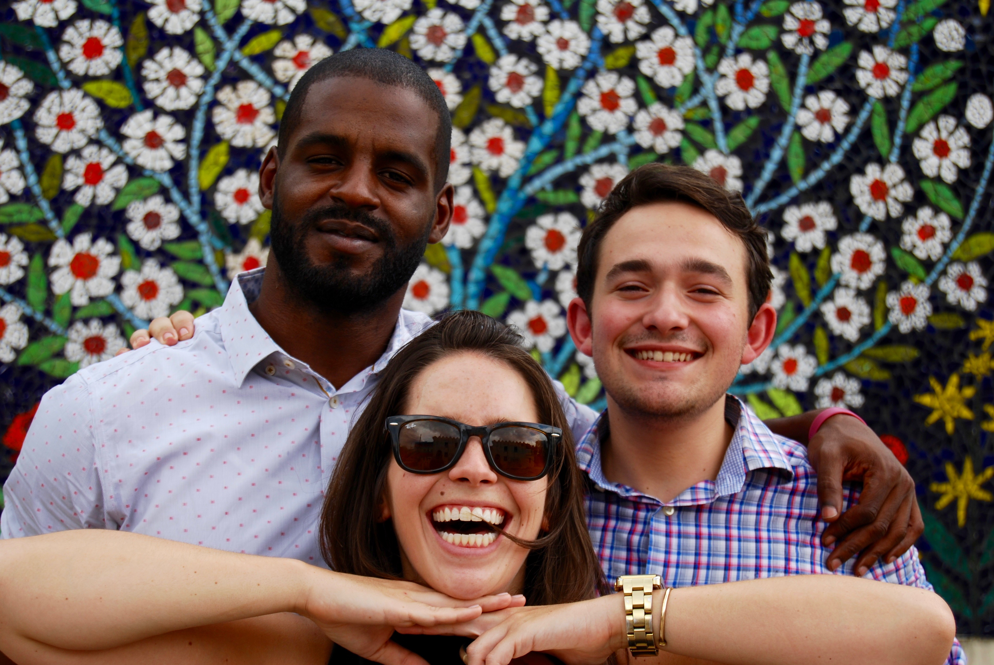 three students smiling in front of floral mural