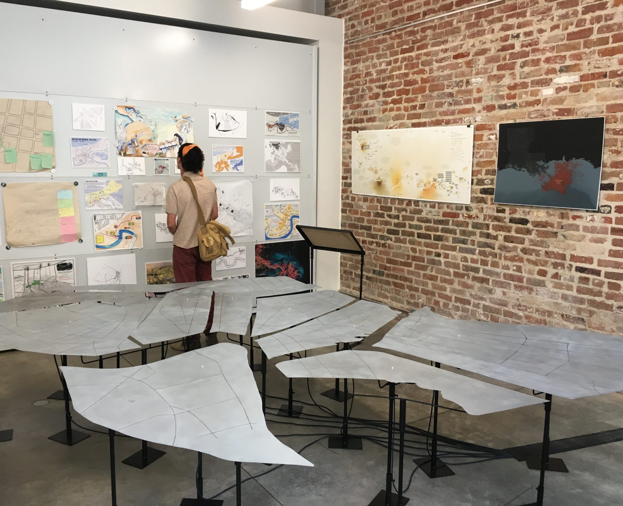 An individual looks at an exhibit of papers on a wall inside a small studio space with a brick wall on the right