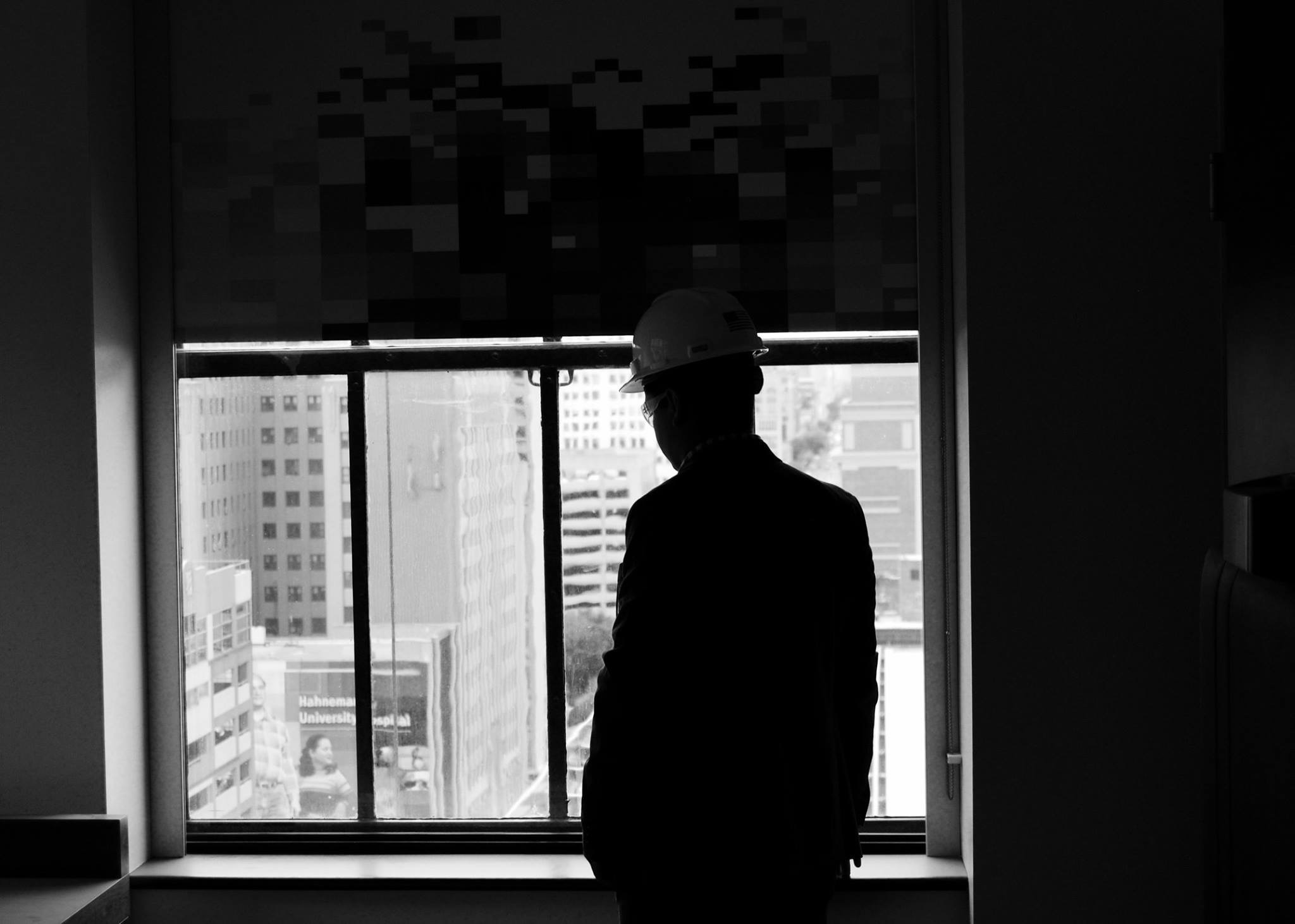 person in hard hat and suit looking out a window at skyscrapers
