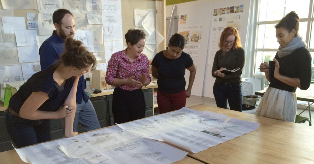 Six faculty and students look down at drawings and papers spread out on top of a large table