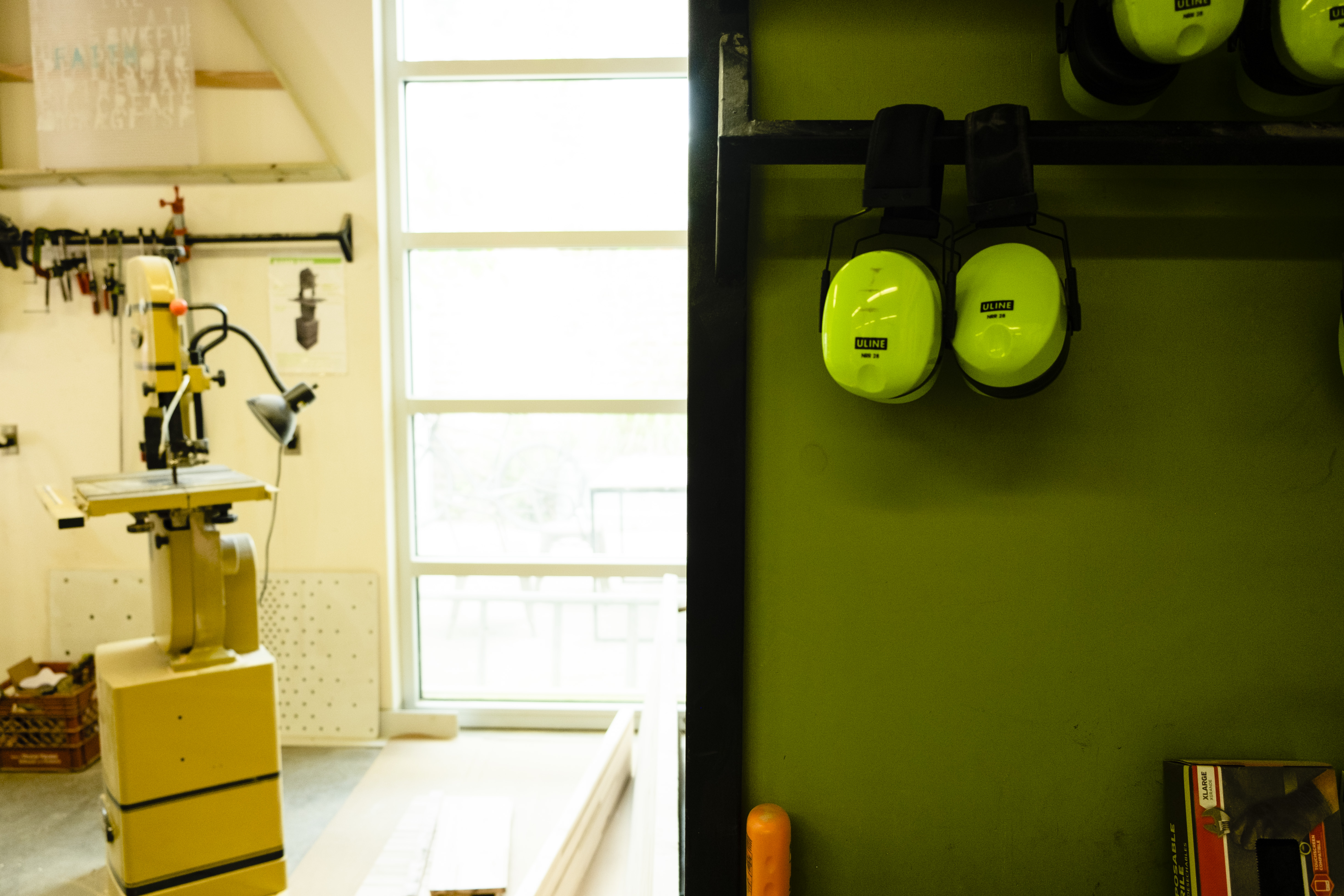 view inside a shop with a large cutting machine in the background and a window letting in light and in the foreground two sets of ear-protection earmuffs hanging on a horizontal poll