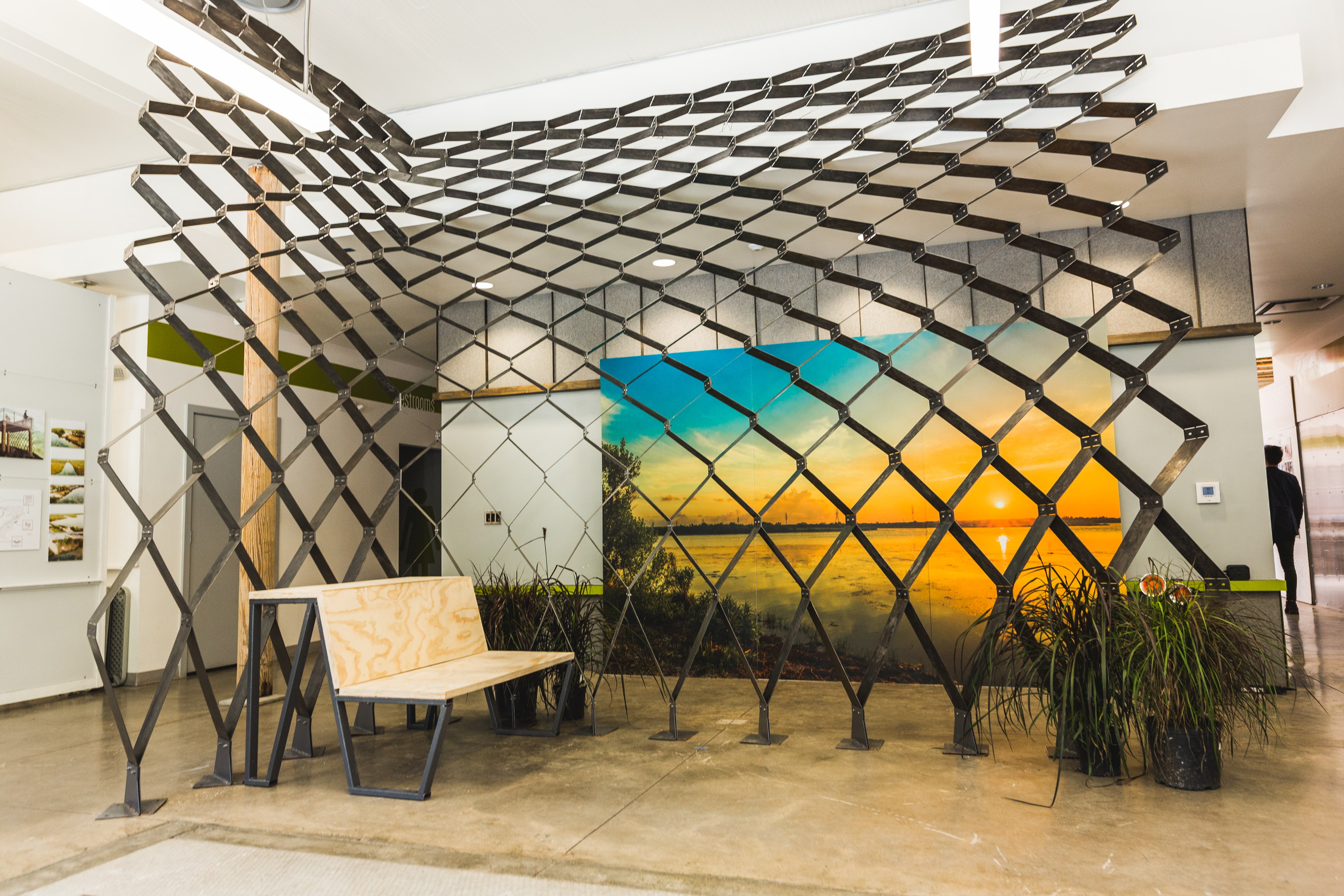Steel screen structure with a wooden bench in front, on display inside a building with a sunset mural behind