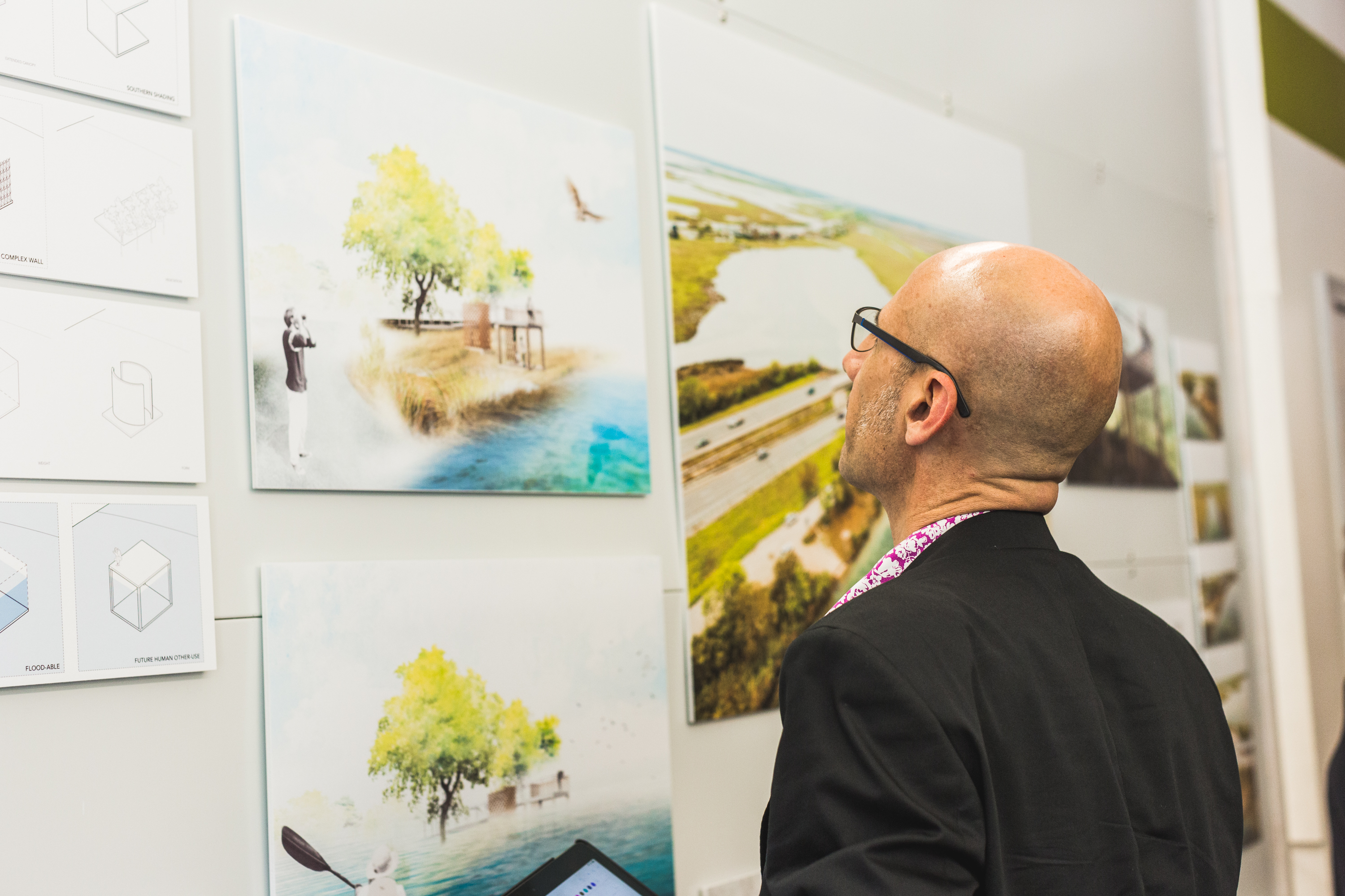 Man in glasses looks at a series of drawings of a bayou-side viewing platform pinned up