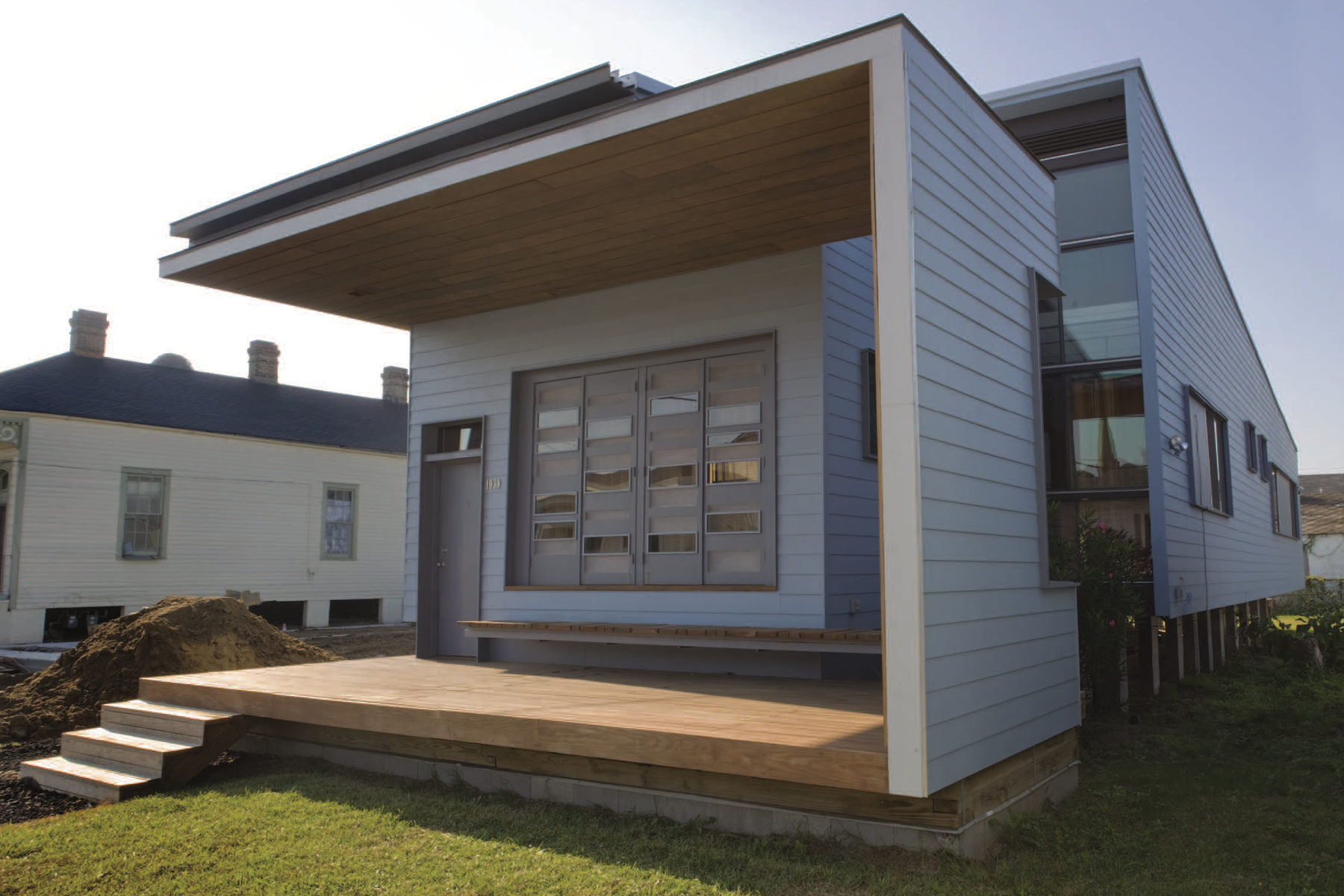 Front view of a modern single-story home with exposed porch and steps down into grass yard