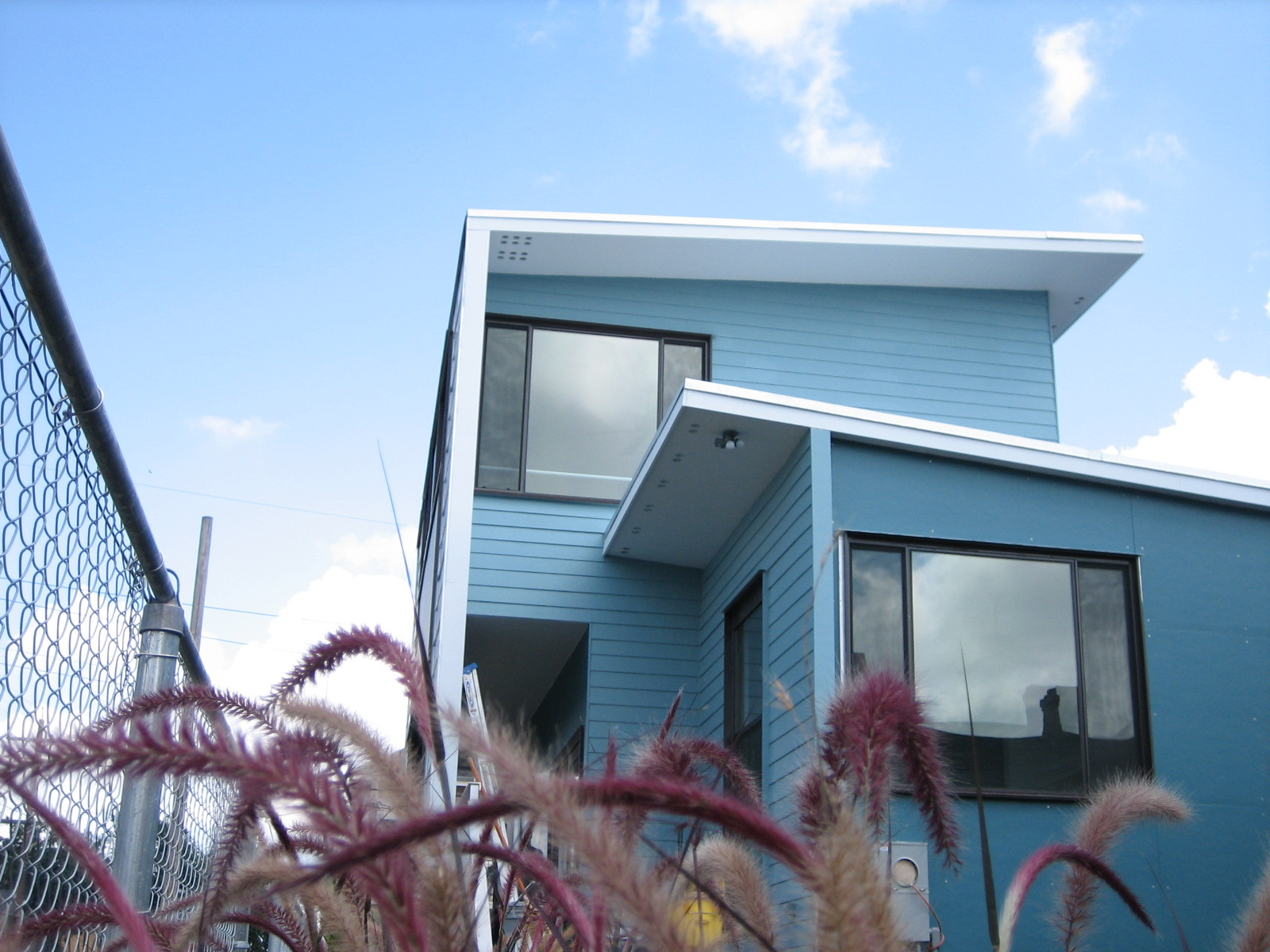 view from below of a modern two-story home with sky and clouds above