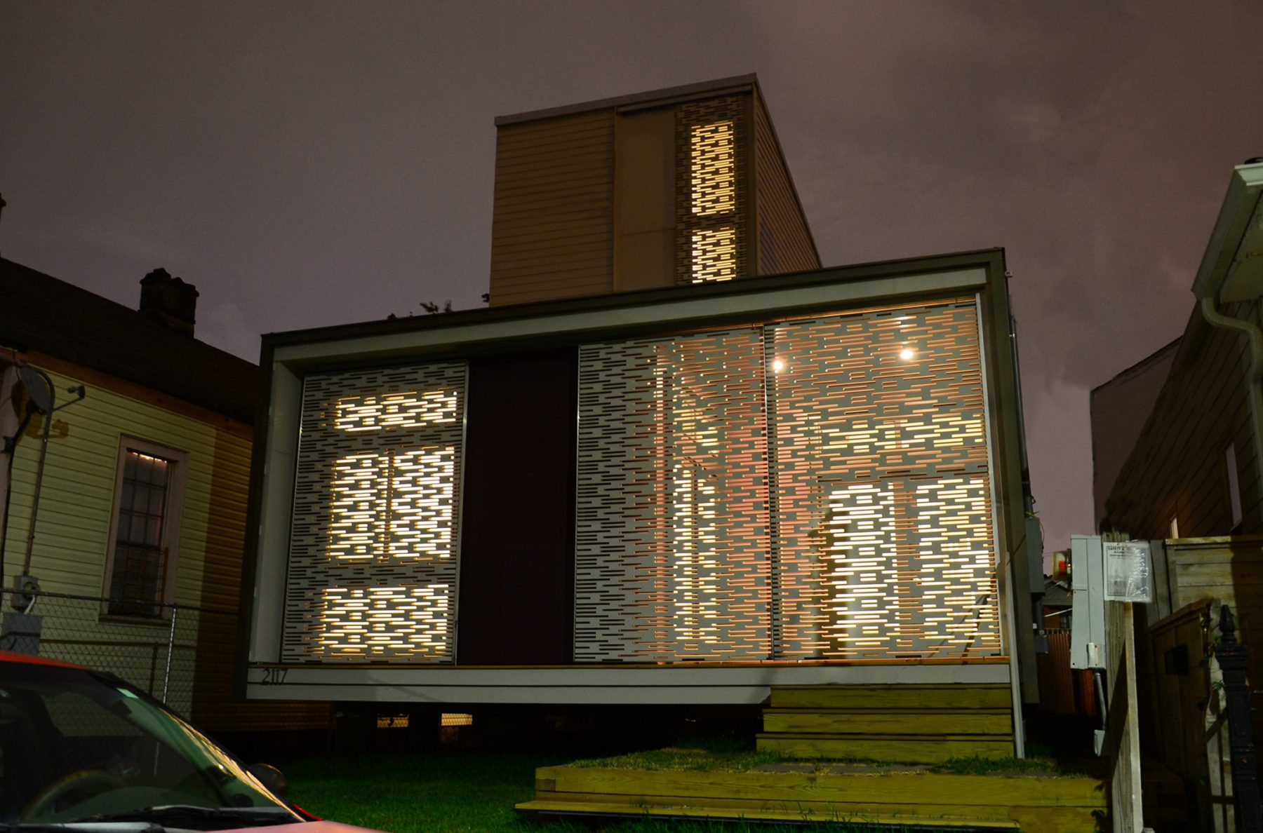 Front view of a modern home at night with lights from inside coming out through screen details