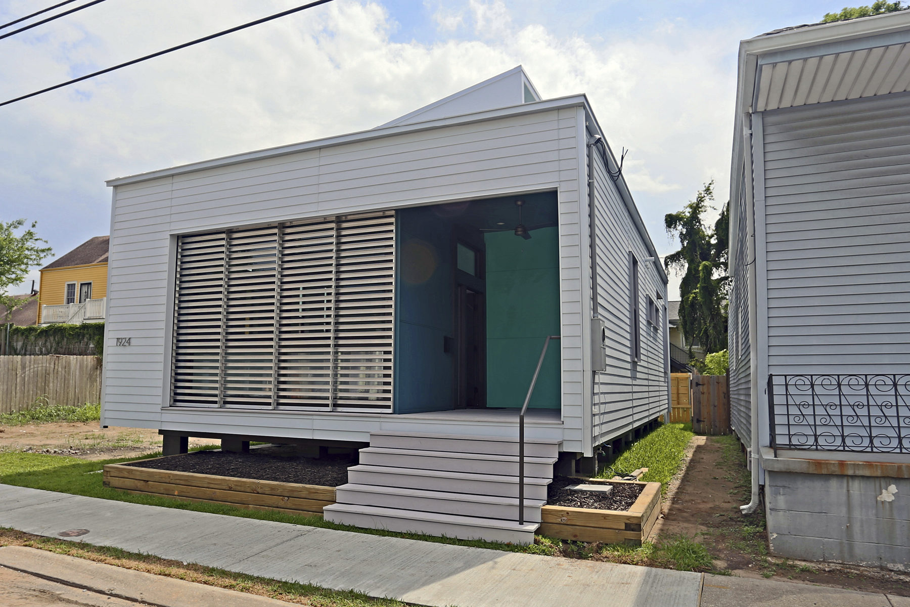 Front view of a modern rectangular home with metal shade screen on the porch