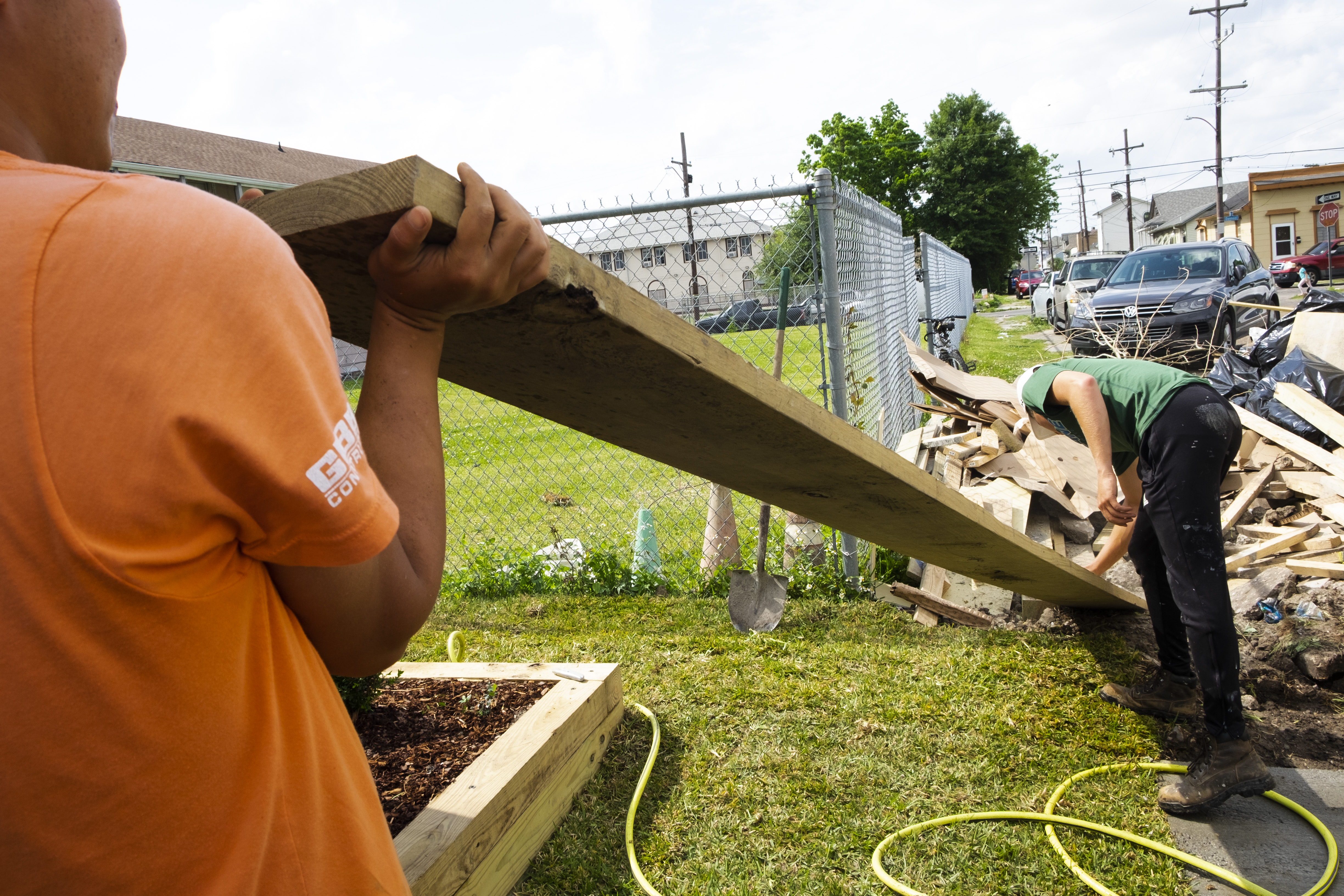 Photo of a first person perspective, lifting a long piece of wood on a construction site