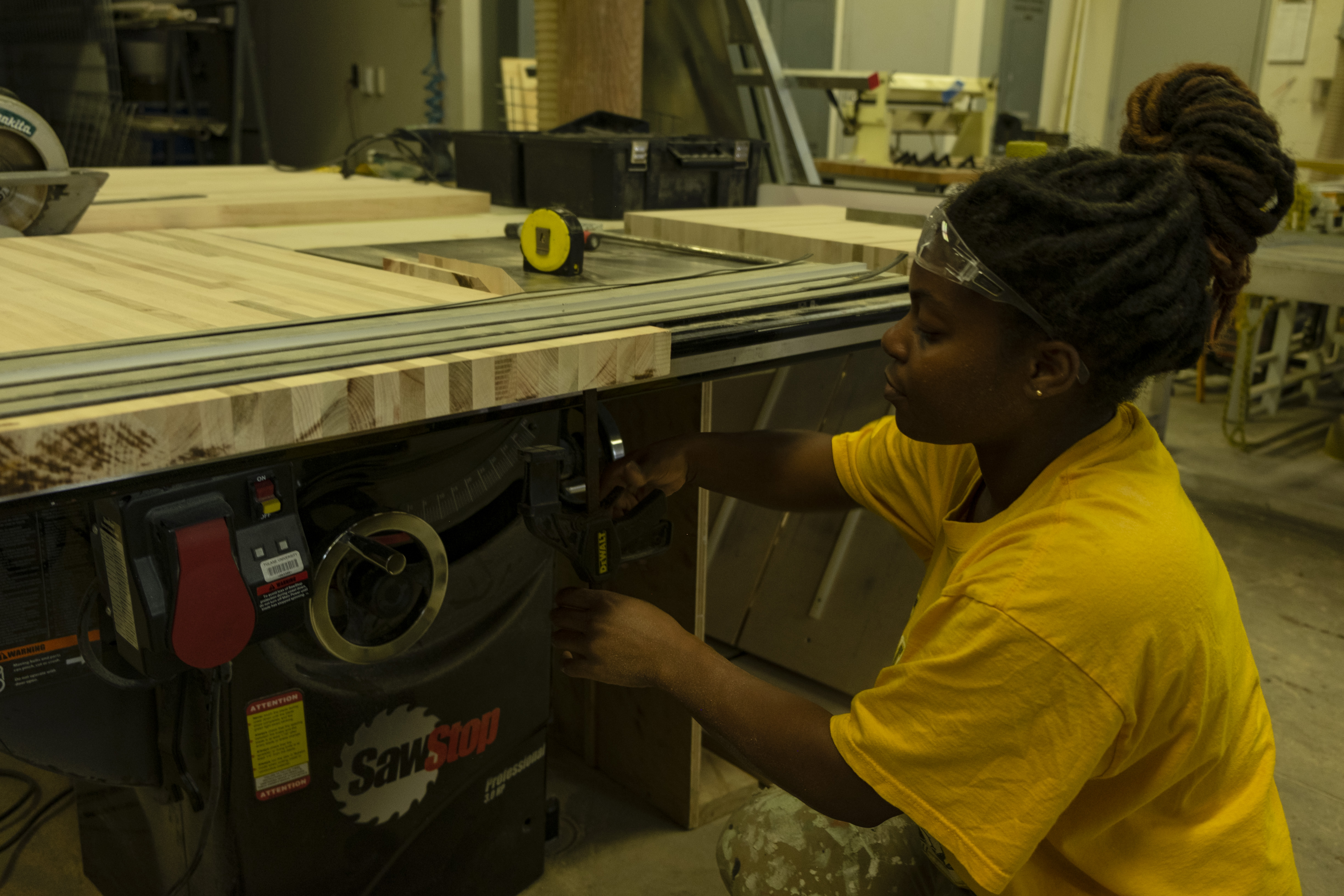 Student in safety googles kneels down at a work table to set up a sawstop.