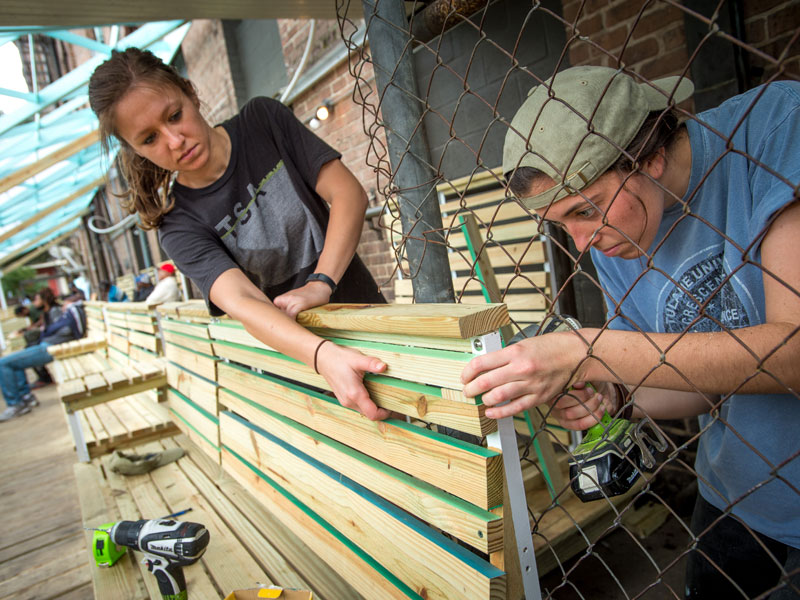 Close up view of two female students using power tools to install wooden benches in front of a brick building
