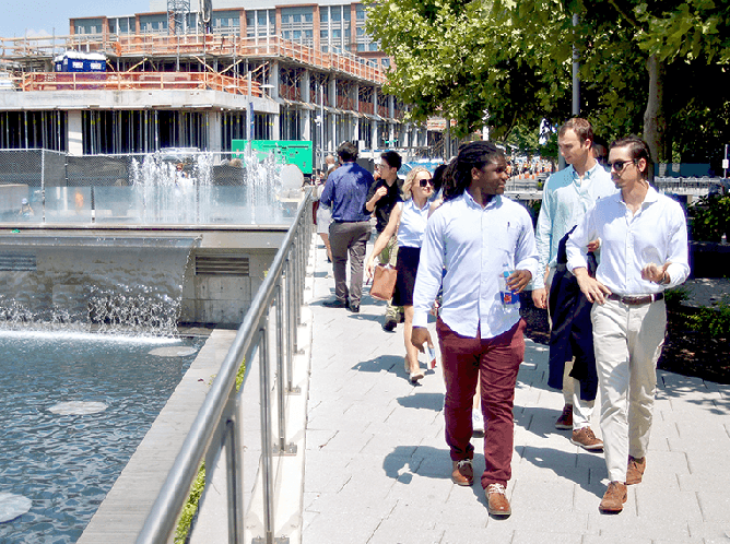 Graduate students walk next to a water feature in a downtown setting with building construction in the background
