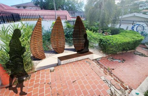 Rendering of a memorial exhibit with three vertical wood panels cut to look like leaves in a courtyard
