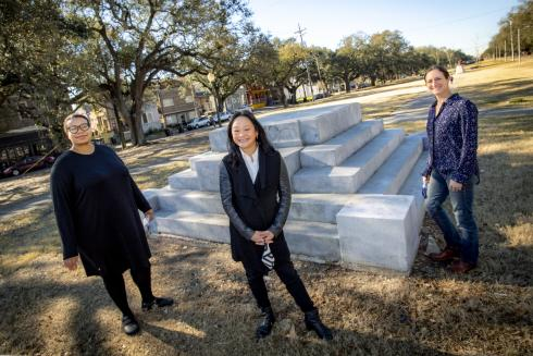 Three female Tulane faculty stand outdoors in front of a vacant pedestal at the intersection of Canal Street and the newly renamed South Norman C. Francis Parkway. The pedestal was home to the Jefferson Davis Monument until it was removed in 2017.