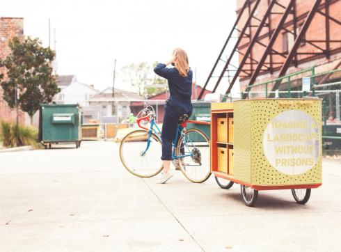 Photo outdoors in a parking lot with a student sitting on a bike that has an attached cart with drawers and cabinets
