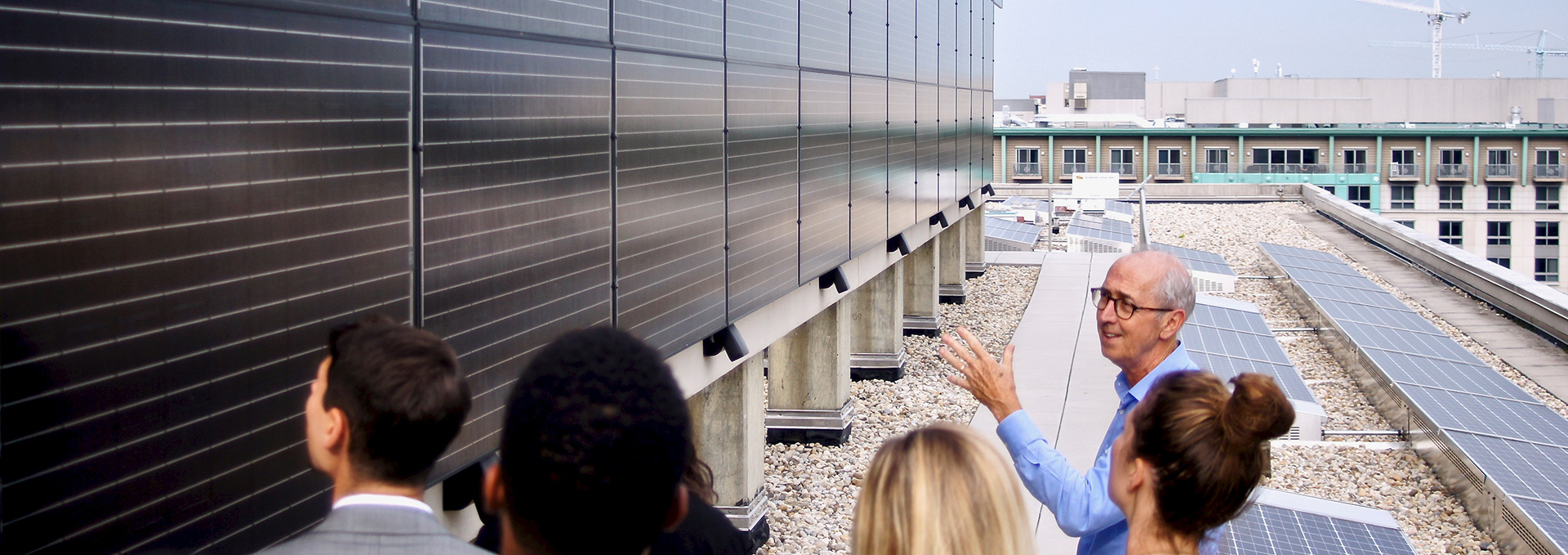 Photo on of a group of people on a rooftop looking at a large wall of solar panels on the left of them